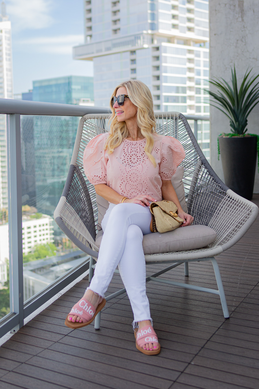girl with sunglasses, white jeans, puffy sleeve top and chair